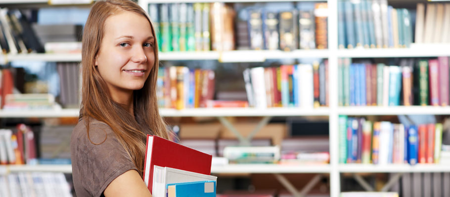 young student girl with books in library