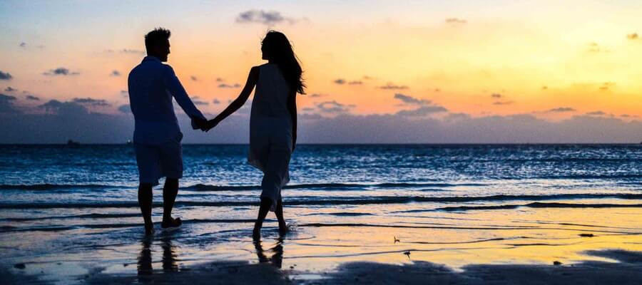 Man and woman holding their hand and walking on the beach at dawn