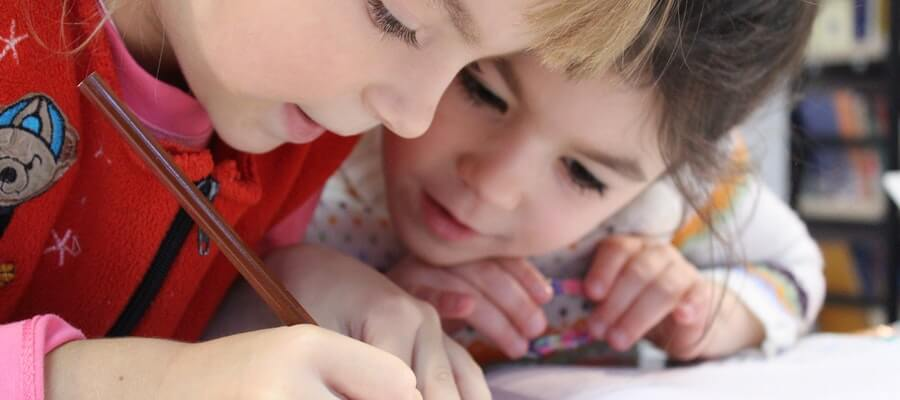 Two kids writing on a school desk