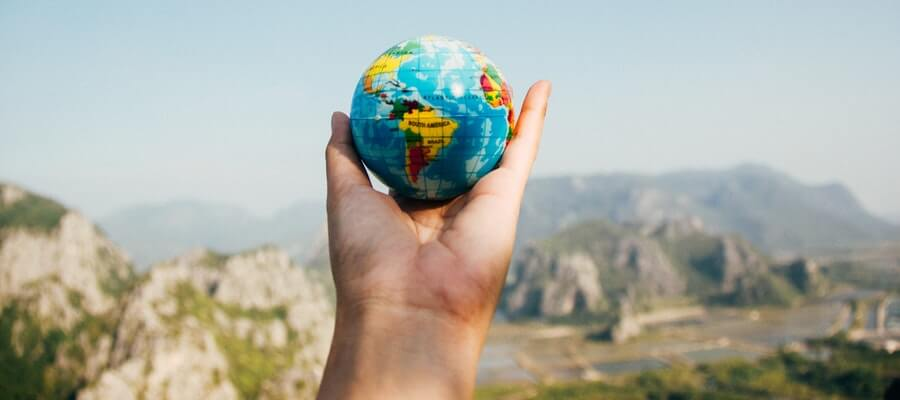 Hand holding a small world globe
